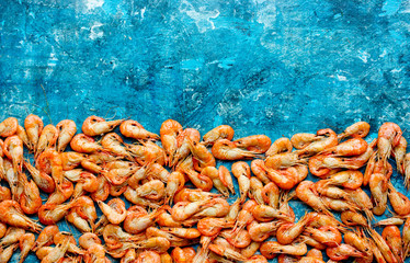 Many small boiled shrimps on a blue background