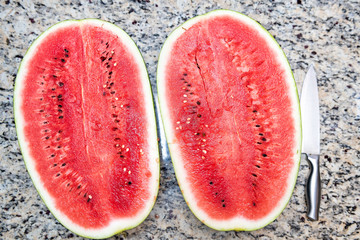 Closeup table lay flat top view of two halfs, halves of red watermelon cut in half with seeds, knife on kitchen granite countertop
