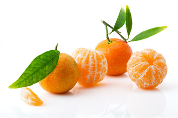 Ripe and juicy mandarin with green leaves close-up