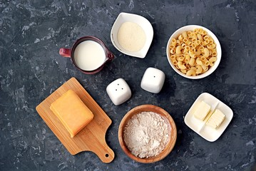 Ingredients for the preparation of macaroni and cheese: dry pasta, orange cheddar cheese, wheat flour, bread crumbs, milk, butter, salt, pepper
