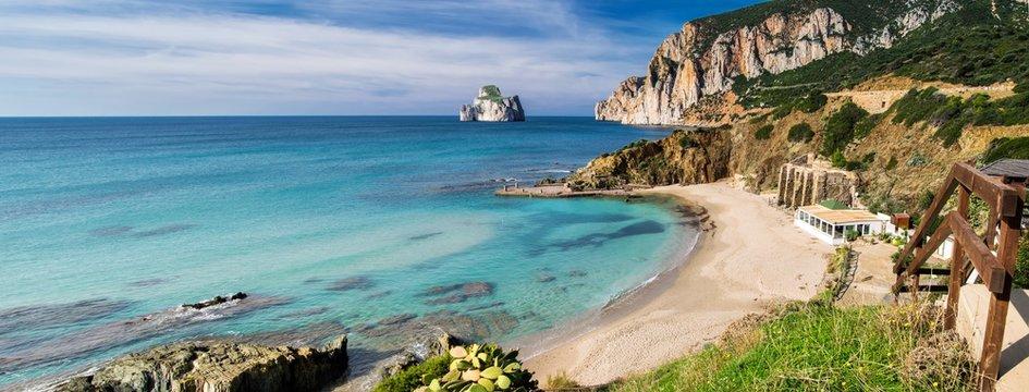 Suggestiva cornice scenografica dell'insenatura di Masua, con vista sull'Imponente roccia del Pan di Zucchero, lungo la costa dell'Iglesiente a sud ovest della Sardegna, Italia.