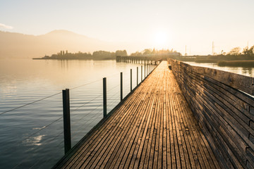 long wooden boardwalk pier over water in golden evening light with a mountain landscape silhouette in the background