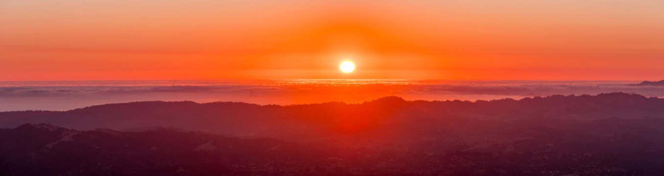 Fiery sunset over a sea of clouds as seen from the top of Mt Diablo, north San Francisco bay area, California (some of San Francisco's buildings visible under a layer of clouds)