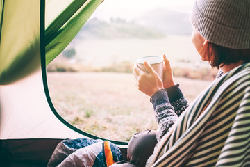 Happy female with cup of hot tea sits in camping tent, looks out and enjoys a new day beginning