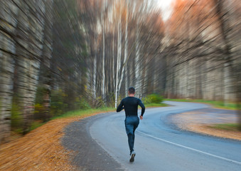 Runner in autumn Park at dawn with blurred background movement.
