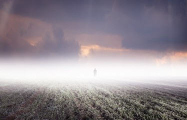 Silhouette of strange man standing in distant fog