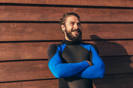 Male surfer lifestyle portrait. Man in wetsuit with bodyboard surfing equipment