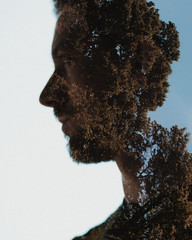 Double exposure of mans face with trees