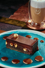 Brownie cake with whole nuts and cappuccino. Chocolate cake with hazelnuts on a blue plate on a background of copper plates. Close up