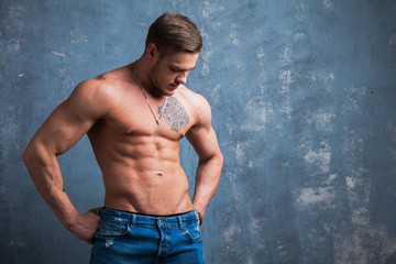 Sexy muscular male model at studio. Young budybuilder fit strong sporty man posing to camera. Guy with naked torso.