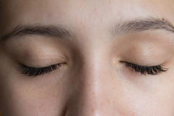 Eyelash Extension Procedure. Woman Eyes with Long false Eyelashes. Close up macro shot of fashion eyes in beauty salon.