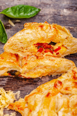 Puff pastry with cherry tomatoes, mozzarella cheese and basil on wooden rustic table. Close up