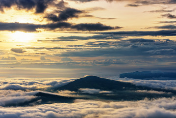 Beautiful nature landscape the sun is above the sea fog that covers the mountains and bright sky during sunrise in the winter at viewpoint of Phu Ruea National Park, Loei province, Thailand.