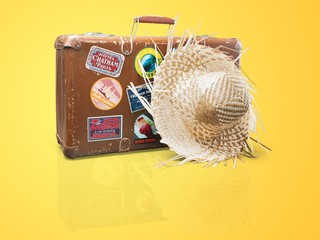 Old vintage travel case and straw hat isolated on white