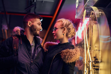 A beautiful girl and handsome man standing in the night on the street.