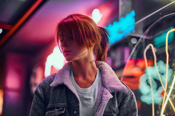 Stylish redhead girl standing in the night on the street. Illuminated signboards, neon, lights. Fotomurales