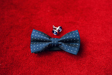 Men's accessories. Blue bow-tie and cufflinks isolated on red background. Groom details