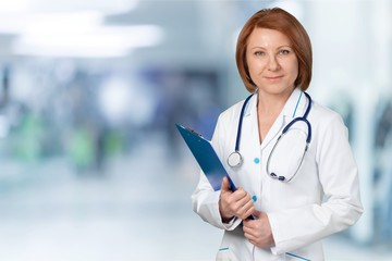Attractive young female doctor with blurred hospital interior on