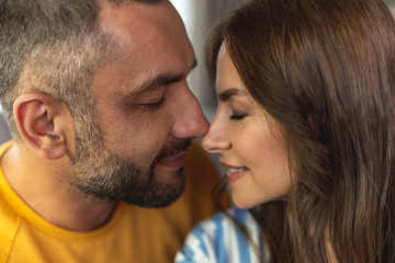 Close up of happy man and woman making romantic photo with closed eyes while touching each other noses