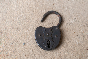 Old weathered grunge retro open padlock closeup on solid stone surface background