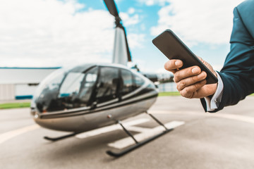Laconic image of the modern smartphone in male hand with new helicopter in the foreground