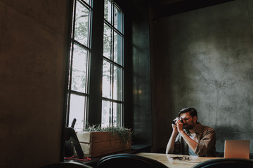 Side view concentrated bearded man taking photo on camera while sitting at table in cozy cafe
