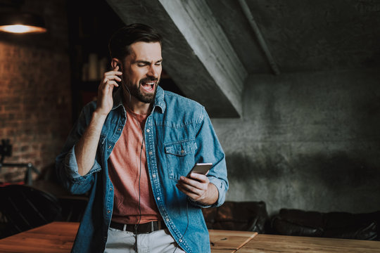 Portrait of happy bearded man listening music with earphones while singing song. He watching at phone during entertainment indoor