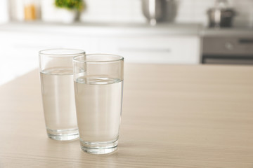 Glasses of fresh water on table indoors. Space for text