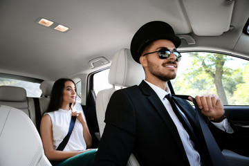 Young businesswoman with handsome driver in luxury car