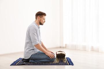 Muslim man with Koran praying on rug indoors. Space for text