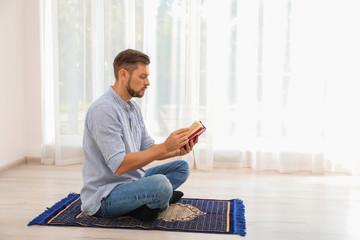 Muslim man reading Koran on prayer rug indoors