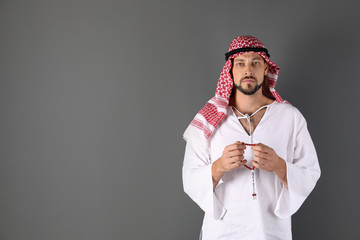 Muslim man praying on gray background. Space for text
