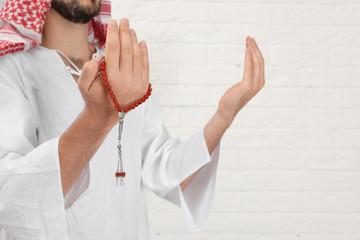 Muslim man praying near brick wall, closeup