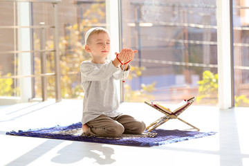 Little Muslim boy with misbaha and Koran praying on rug indoors