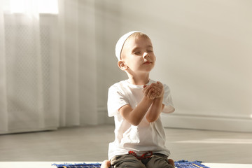 Little Muslim boy with misbaha praying indoors