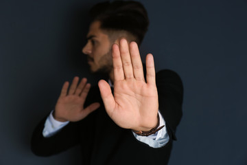 Man showing stop gesture on dark background. Problem of sexual harassment at work