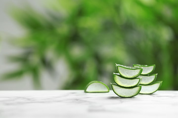 Slices of aloe vera on table against blurred background. Space for text