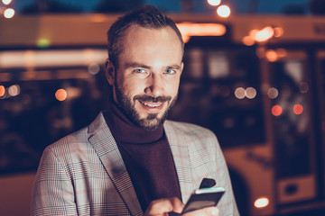 Attractive cheerful young man feeling glad and smiling while standing with modern smartphone in his hand and looking at you