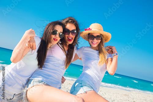 291c980b1f4 Tres mujeres muy sexys con camiseta blanca saltando y disfrutando un día de  verano.