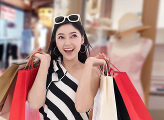 cheerful woman holding shopping bag at mall