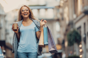 Waist up portrait of beautiful middle-aged lady in glasses holding cup of coffee and shopping bags. She is looking at camera and laughing