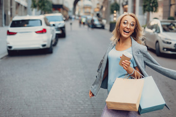 Waist up portrait of beautiful middle-aged lady in glasses holding cup of coffee and shopping bags while looking at camera and laughing