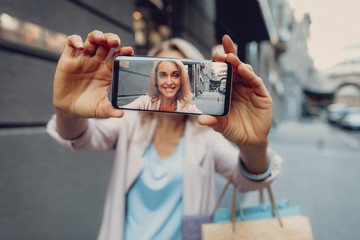 Elegant middle-aged lady taking photo with smartphone while looking at camera and smiling. Focus on phone display with woman picture