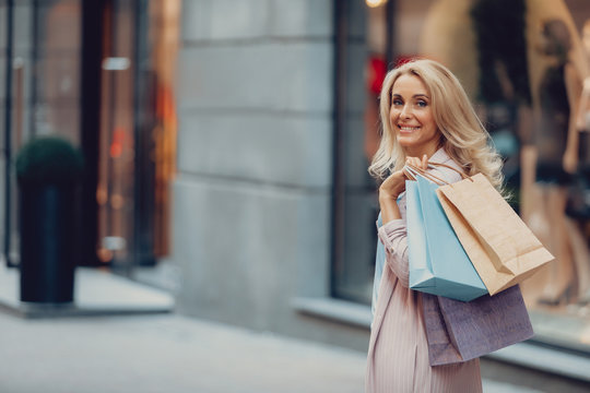 Waist up portrait of charming woman holding colorful shopping bags. She is looking at camera and smiling