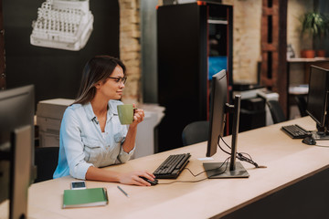 Side view portrait of attractive lady holding cup of coffee and using computer mouse. She is sitting at office desk with cellphone, pencil and notebook