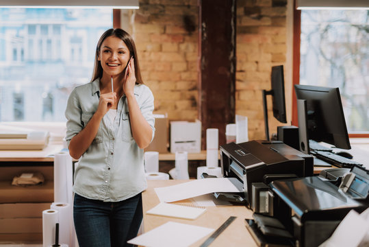 Portrait of charming woman in blue shirt having phone conversation while standing near office desk with printer. She is looking away and smiling