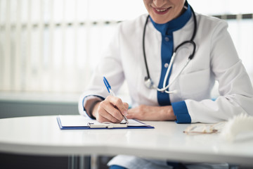 Concept of professional help in healthcare system. Close up portrait of smiling female doctor in medical uniform making notes in her workplace