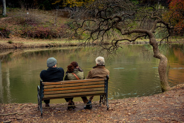 People seat on wooden bench by the lake in nature