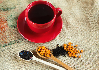 Vitaminic healthy sea buckthorn tea in red cup with fresh raw sea buckthorn berries and black tea in wooden spoons over sackcloth background. warm winter  organic drink, health food concept