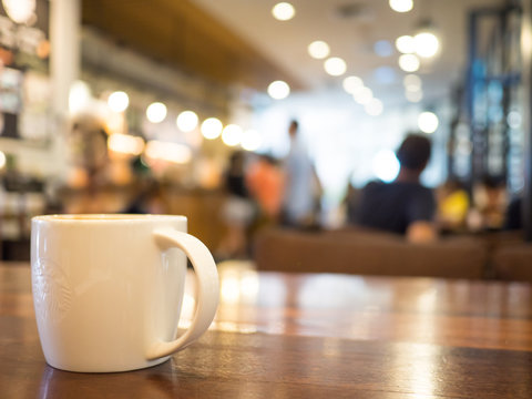 Chiang mai, Thailand-September 22,2018: Hot coffee cappuccino in white cup starbucks on wooden table and blurred background cafe stores.
